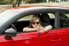 Attractive woman smiling proud sitting at driver seat holding and showing car key in new automobile buying and renting Royalty Free Stock Images