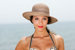Attractive woman smiling with a sun hat on a tropical beach Royalty Free Stock Photography