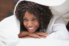 Attractive woman smiling under the duvet Stock Photo