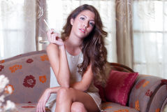 Attractive woman smoking a cigar, sitting on living room Stock Photos