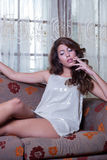 Attractive woman smoking a cigar, sitting on living room Stock Photography