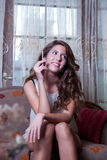 Attractive woman smoking a cigar, sitting on living room Royalty Free Stock Photography