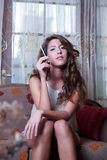 Attractive woman smoking a cigar, sitting on living room Royalty Free Stock Photo