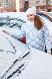 Attractive woman and snowy car with drawing heart shape. On glass royalty free stock photo