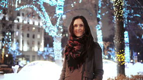 Attractive woman at snowy Christmas night smiles looking at the camera in front of park trees decorated sparkling lights Stock Photos