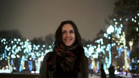 Attractive woman at snowy Christmas night smiles looking at the camera in front of park trees decorated sparkling lights stock footage