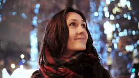 Attractive woman at snowy Christmas night smiles looking at the camera in front of park trees decorated sparkling lights stock video