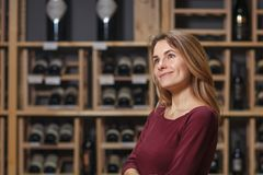 Attractive woman sommelier in wine cellar background.  stock photos