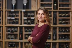 Attractive woman sommelier in wine cellar background.  stock images