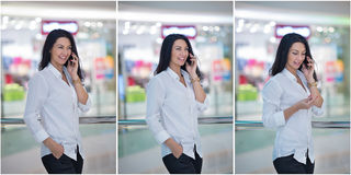 Attractive woman speaking on mobile in mall. Beautiful fashionable young girl in white male shirt posing in modern shopping center Stock Photo