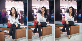 Attractive woman speaking on mobile in mall. Beautiful fashionable young girl in white male shirt sitting on wooden bench. In modern shopping center. Long hair Stock Photography