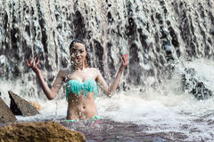 Attractive woman splashes water on waterfall Stock Photography