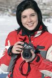 Attractive woman in sport wear holding a camera. Winter outdoors Royalty Free Stock Image