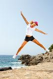 Attractive woman in sportswear jumping outdoors. Stock Image