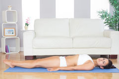Attractive woman in sportswear lying on a blue exercise mat Royalty Free Stock Images