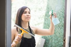 Attractive woman spraying detergent on glass window. Portrait of young maid wearing uniform and apron, cleaning the mirror with spray at the home Royalty Free Stock Photo