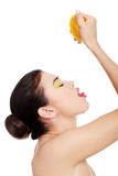 Attractive woman squeezing orange juice straight to mouth. Royalty Free Stock Photo