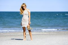 Attractive woman standing barefoot at beach Royalty Free Stock Image