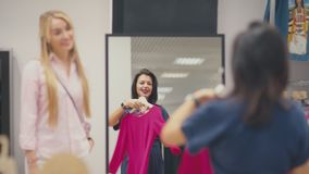 Attractive woman standing in front of a mirror and selects dress stock footage