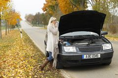 Attractive woman standing helpless beside her broken car. Attractive woman standing beside her broken car in autumn Stock Photos