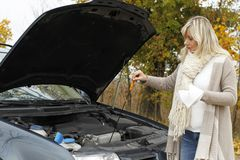 Attractive woman standing helpless beside her broken car. Attractive woman standing beside her broken car controlling oil Stock Photography