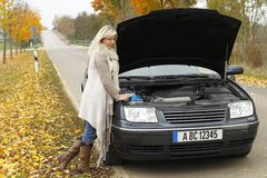 Attractive woman standing beside her broken car. In autumn Stock Photography