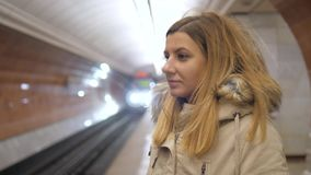 Attractive woman standing in metro and using the smartphone, waiting a train. Young attractive brunette woman in a warm autumn jacket stands in the subway and stock video