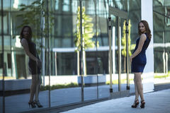 Attractive  woman standing near the business centre is reflected in the glasses. Stock Photography