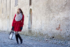 Attractive woman standing over old wall in Tallinn Royalty Free Stock Photo