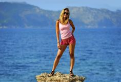 Attractive woman standing at rock feeling free in front of the sea. Happy young blond attractive woman with sunglasses standing at rock, feeling  free in front Stock Photography