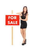 Attractive woman standing by a for sale sign Stock Image