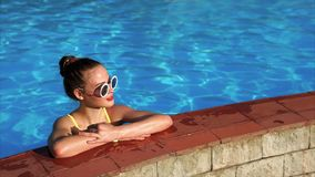 Attractive woman standing on the side of swimming pool and enjoying vacation. Attractive expressive woman with sunglasses stock footage