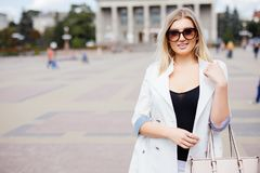 Attractive woman standing in an urban square in front of a large historic building looking at the camera with a warm friendly smil. E with copy space Stock Images
