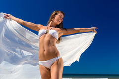 Attractive woman stands in the sun on beach stock image
