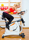 Attractive woman on stationary bike Royalty Free Stock Photography