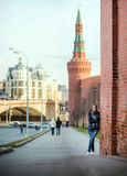 Attractive woman stay near the Kremlin wall on Red Square, Moscow, Russia. Cold season. Royalty Free Stock Photo