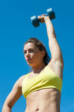Attractive woman stretching with dumbbells on playground Royalty Free Stock Photos