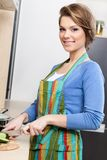 Attractive woman in striped apron chops vegetables Stock Photo