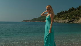Attractive woman strolls along coast on sunny day outdoors. stock video
