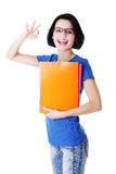 Attractive woman/student holding files and showing OK. Royalty Free Stock Photo