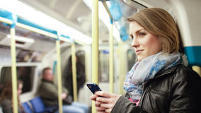 Attractive woman on a subway train smiles at something off camera Royalty Free Stock Photo