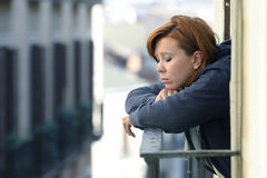 Attractive woman suffering depression and stress alone in pain smoking at balcony Royalty Free Stock Photos