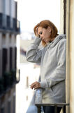 Attractive woman suffering depression and stress outdoors at the balcony Stock Image