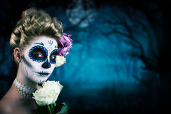 Attractive woman with sugar skull make-up. In front of a creepy forest scene Stock Image