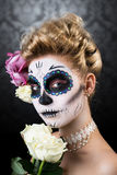 Attractive woman with sugar skull make-up. And a rose royalty free stock photo