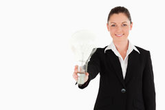 Attractive woman in suit holding a light bulb Royalty Free Stock Photography
