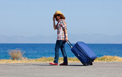 Attractive woman with suitcase on  beach Royalty Free Stock Photos