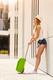 Attractive woman with suitcase relaxing after arrival Royalty Free Stock Photos