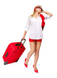 Woman pulling red suitcase talking phone over white. Woman pulling red vacation suitcase, talking on phone. Isolated over white background Stock Image