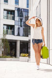 Attractive woman with suitcase walking after arrival. Travel, adventure, teenage journey concept. Walking woman wearing denim shorts, white top and sun hat Stock Photography